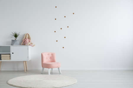 Photo for Scandi style girl's bedroom with a plant standing on a white cupboard next to a pink, chic chair, and a white circular carpet - Royalty Free Image