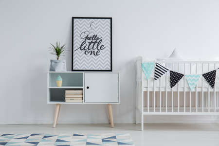 Foto de Modern Scandinavian child's bedroom interior with a small bed, monochromatic carpet, and a poster with text standing on a cupboard next to a plant - Imagen libre de derechos