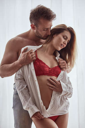 Photo pour Handsome husband in jeans undressing his pretty wife in red lingerie - image libre de droit