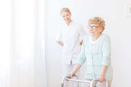 Foto de Smiling nurse takes care about senior woman who uses walking frame in hospital - Imagen libre de derechos