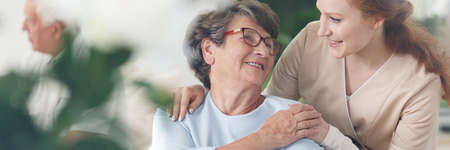 Photo pour Professional helpful caregiver comforting smiling senior woman at nursing home - image libre de droit