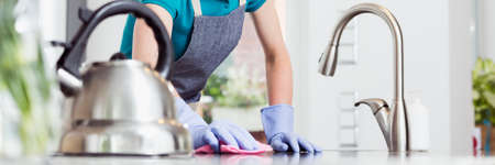Photo pour Woman in rubber gloves rubbing the countertop with a pink dishcloth - image libre de droit
