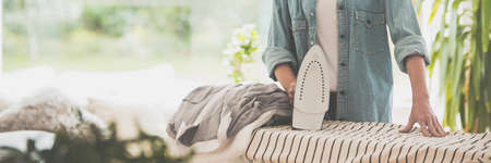 Photo for Young woman in a jean jacket ironing clothes - Royalty Free Image