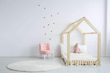 Photo for Modern children's furniture in a spacious bedroom with star stickers on the white wall, and a pastel pink comfortable chic chair next to a wooden bed - Royalty Free Image