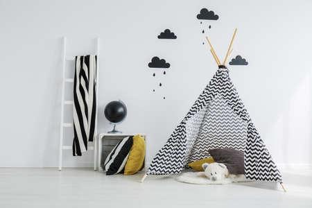Foto de Stylish,patterned teepee with a white teddy bear lying inside it, in a minimalist. scandinavian kid bedroom - Imagen libre de derechos
