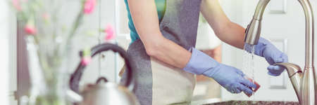 Photo pour Lady in rubber gloves wetting a sponge over an iron kitchen sink - image libre de droit