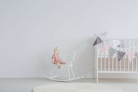 Foto de Stylish scandi design kid's bedroom with a stuffed animal rabbit sitting on a rocking horse next to a decorated baby bed - Imagen libre de derechos