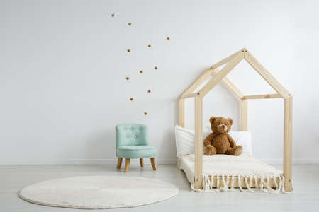 Photo for Elegant mint chair in a spacious, decorated kid's bedroom standing next to a modern wooden bed with a teddy bear sitting on it - Royalty Free Image