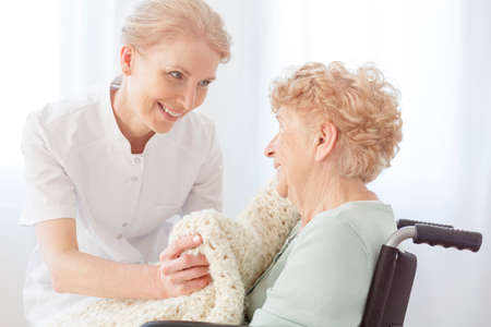Foto de Smiling caregiver gives a beige blanket to pensioner on wheelchair sick on osteoporosis - Imagen libre de derechos