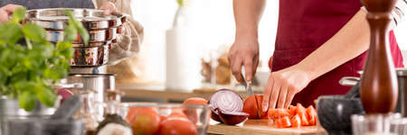 Foto de Young woman preparing delicious homemade tomato sauce for pasta - Imagen libre de derechos