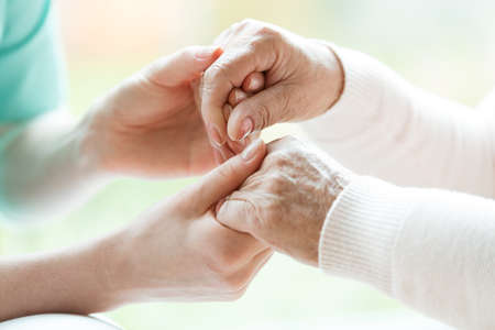 Foto de Photo with close-up of caregiver and patient holding hands - Imagen libre de derechos