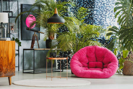 Photo pour Spacious living room with pink plush armchair, telescope and exotic plants - image libre de droit