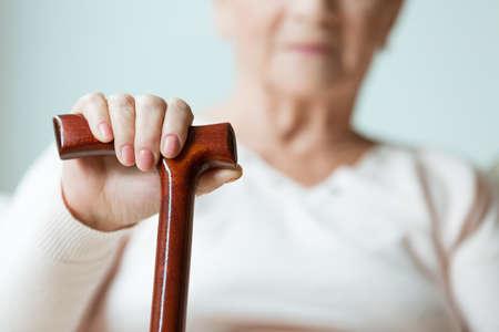 Foto de Sad older lady's hand placed on wooden walking stick - Imagen libre de derechos