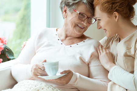 Foto de Elder woman with cup of tea and her friendly caretaker looking in each other's eyes - Imagen libre de derechos