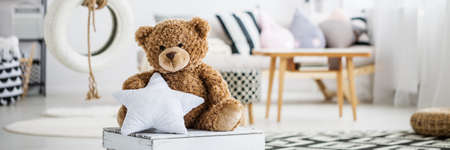 Photo pour Big teddy bear holding a pillow star in girly room - image libre de droit