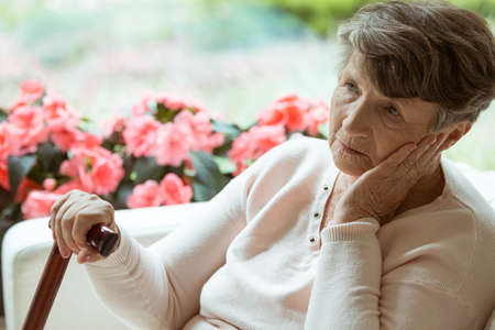 Foto per Sad elder lady sitting on the sofa and worrying about her health - Immagine Royalty Free