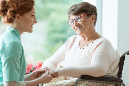 Foto de Young caucasian nurse supporting elder woman with glasses in wheelchair - Imagen libre de derechos
