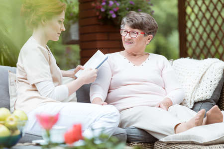 Photo pour Young caregiver reading personal journal of lady with Alzheimer's disease while sitting on garden sofa - image libre de droit