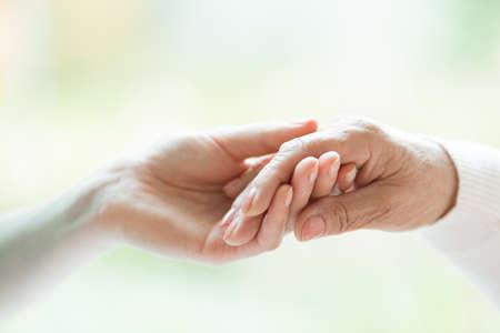 Foto de Close-up photo of young hand holding the older one - Imagen libre de derechos