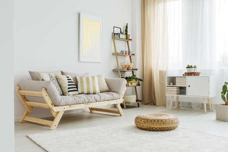 Foto de Material pouf on white carpet in front of grey sofa with patterned pillows - Imagen libre de derechos