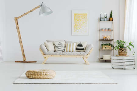 Foto de Grey sofa with patterned pillows in bright living room with big lamp - Imagen libre de derechos