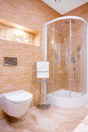 Photo pour Shower in modern bathroom with beige marble and sculpture on wall - image libre de droit