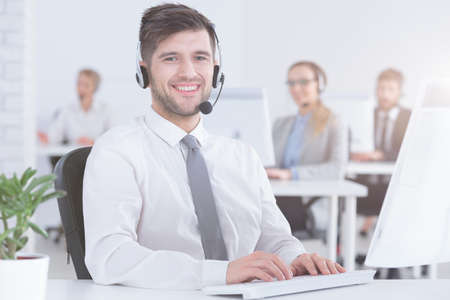 Photo pour Smiling handsome customer service consultant at work in modern office - image libre de droit