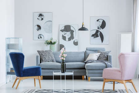 Photo pour Pink and blue armchairs in cozy living room with grey sofa and black vase on small coffee table - image libre de droit