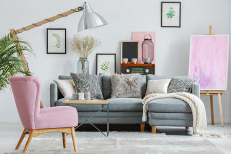 Photo pour Pink armchair on grey carpet in living room with white blanket on grey sofa and designed lamp - image libre de droit