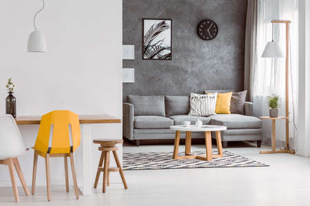 Foto de Yellow chair at wooden table in modern living room with decorative pillows on grey sofa - Imagen libre de derechos