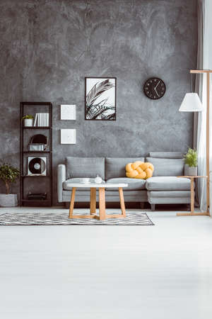 Photo pour Spacious living room with coffee table on carpet in scandinavian style and grey sofa against concrete wall - image libre de droit