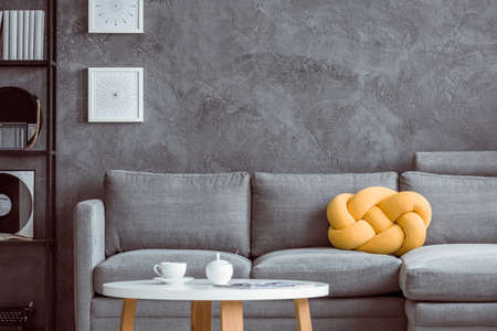 Photo pour White cup on wooden coffee table in living room with yellow pillow on grey settee against concrete wall - image libre de droit