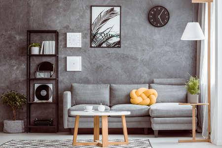 Foto de Black clock and posters on dark wall above grey settee with yellow pillow in cozy living room - Imagen libre de derechos