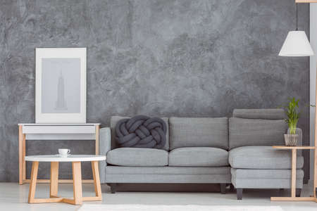 Photo pour Simple poster on wooden shelf next to grey couch set with black knot pillow in dark living room - image libre de droit