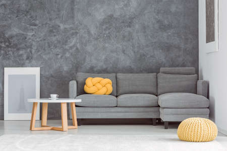 Photo pour Yellow pouf in front of grey sofa against concrete wall in living room with designed coffee table - image libre de droit