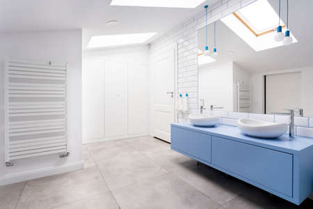 Photo for Cozy attic bathroom with grey floor, blue washbasin cabinet and heater - Royalty Free Image