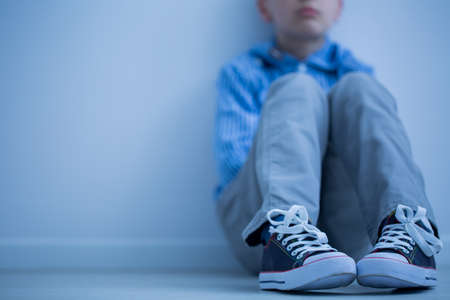 Foto de Sad boy in sneakers with asperger's syndrome sits alone in his room - Imagen libre de derechos