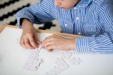 Foto de Boy in striped shirt is doing puzzles on white desk at home. Autistic child therapy concept - Imagen libre de derechos