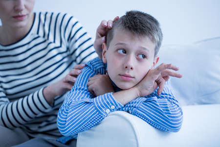 Foto de Mother in striped shirt is worried about her autistic child lying on white sofa - Imagen libre de derechos