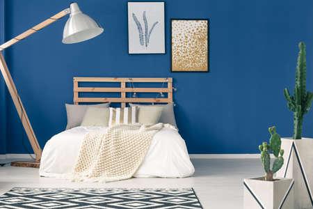 Photo pour Comfy bedroom with wooden frame, navy blue walls, light bedding - image libre de droit