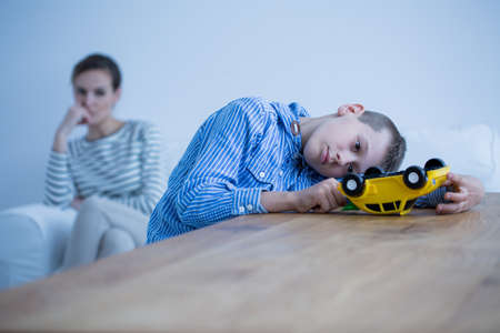 Foto de Sad boy sick of autism plays with yellow toy car while his mother is looking at him - Imagen libre de derechos