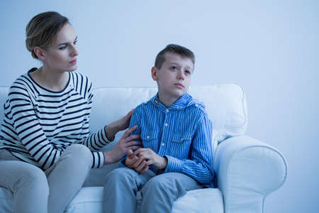 Foto de Worried mom tries to turn attention of sick son sitting on white sofa - Imagen libre de derechos
