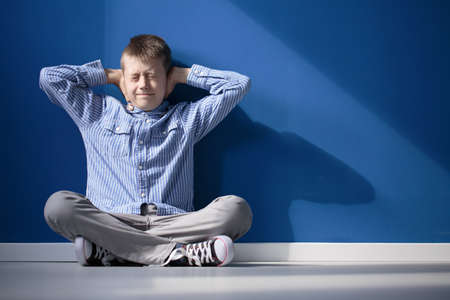 Foto de Boy with hypersensitive auditory is covering ears while siting on floor in empty room - Imagen libre de derechos