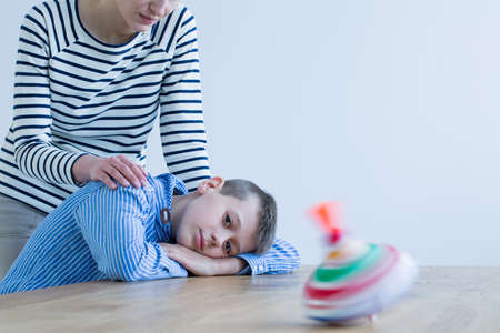 Foto de Mother in striped shirt hugs son lying on desk and looking at colorful toy - Imagen libre de derechos