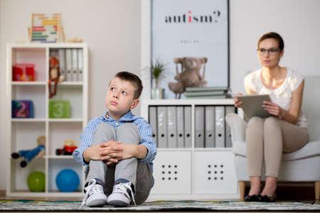 Foto de Psychologist in glasses is looking at kid sick of autism sitting on carpet in classroom. Autistic child therapy concept - Imagen libre de derechos