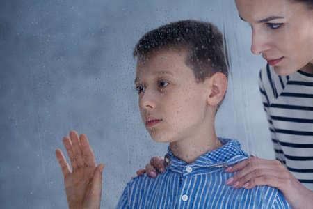 Foto de Worried mother comforts her sad autistic son standing by window during rainy weather - Imagen libre de derechos