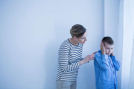 Foto de Boy in blue shirt doesn't want to hear while his mother in striped shirt is talking to him - Imagen libre de derechos