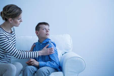 Foto de Mom in striped shirt calms her son who has panic attack while sitting on white sofa - Imagen libre de derechos