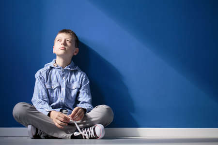 Foto de Thoughtful autistic boy sits with crossed legs on white floor against blue wall - Imagen libre de derechos