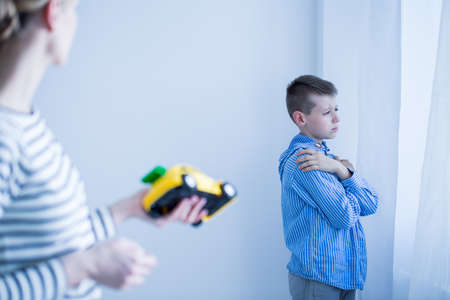 Foto de Mother in striped shirt tries to encourage sick son to play with yellow toy car - Imagen libre de derechos
